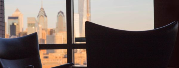 Two leather chairs in front of the Philadelphia skyline in a corner office